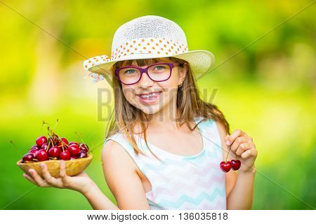 Child with cherries. Little girl with fresh cherries. Young cute caucasian blond girl wearing teeth braces and glasses. Portrait of a smiling young girl with bowl full of fresh cherries.