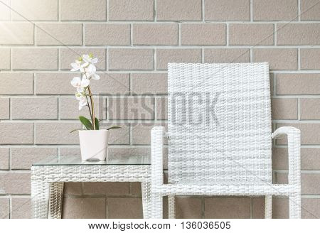Closeup artificial plant with white orchid flower on pink flower pot on wood weave table with wood weave chair on blurred brown brick wall texture background beautiful interior in relaxation concept