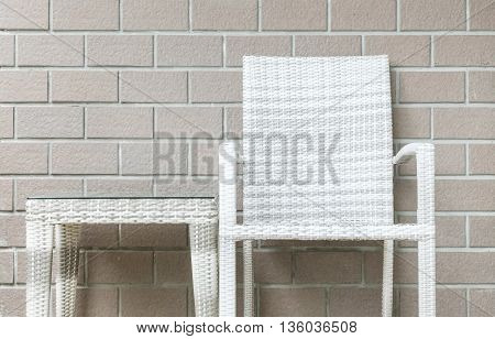 Closeup wood weave table and wood weave chair on blurred brown brick wall texture background beautiful interior in relaxation of house concept