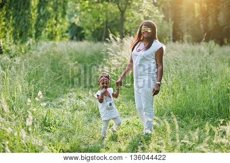 Black Mother And Daughter Holding Hand At Park