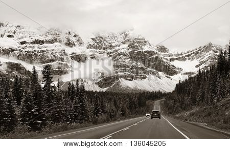 Highway with snow capped mountain forest and car in Banff National Park, Canada