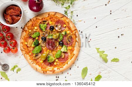 Delicious pizza with ingredients served on wooden table. Shot from aerial view, copyspace for text