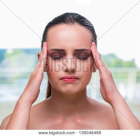 Young woman holding her temples with headache