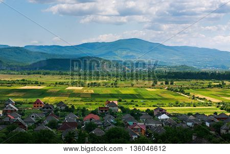 Country landscape in the mountain valley with houses on blue sky