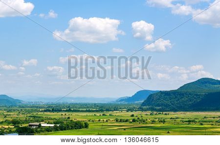Country landscape in the mountain valley with farmland on blue sky