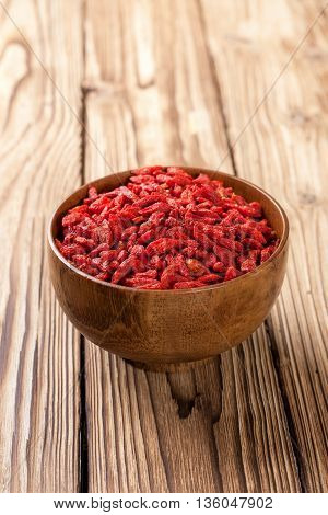 Wooden bowl with dried goji berries on a wooden background. Superfud