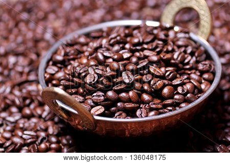 Coffee beans in a copper plate on table