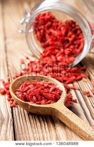 Wooden spoon with goji berries on wooden background. Superfud