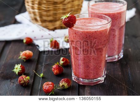 two glass of cold strawberry milk shake on a wooden background
