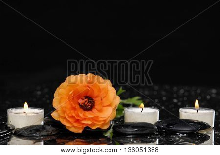 Lying down ranunculus with candle and therapy stones