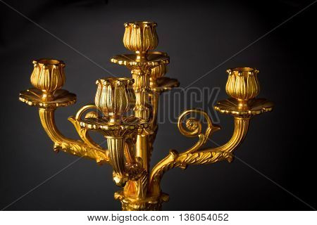Antique bronze chandelier - candle holder on a black background. Bronze and marble. Detail