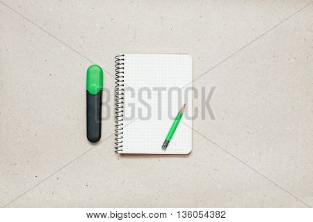 Empty notepad on paper background with green marker and pencil
