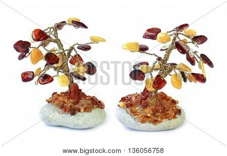 Tree statuette on the stone made of amber drops isolated over white background