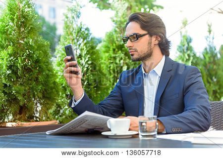 Man newspaper using mobile phone table cafe cup suit