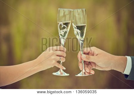 Wedding wineglasses in hands of newlyweds on the picnic, wedding day