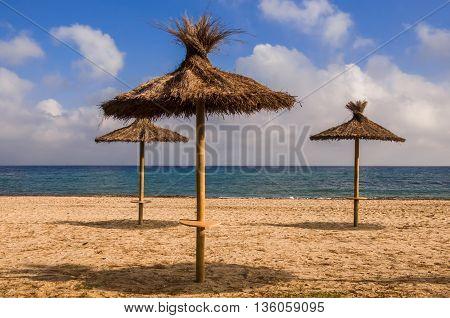 Three straw sunshades tranquil sea blue sky with clouds. Lonely mediterranean beach. Summer travel destination.