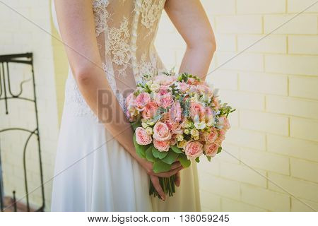 wedding bouquet in bride's hands. Bride standing on the balcony
