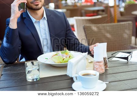 Confident young businessman talking on mobile phone in restaurant. He is sitting at table near a plate of salad and cup of coffee