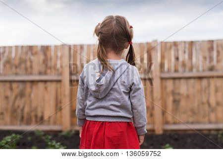 Little girl standing in front of a wooden fence in the garden on a summerday.