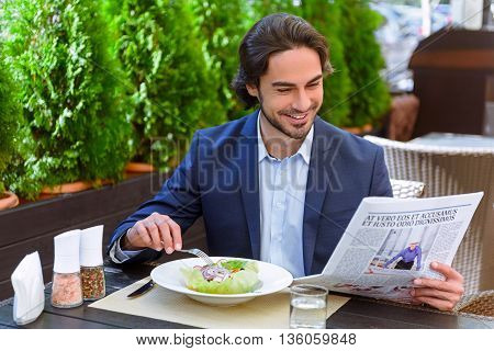 Successful young businessman eating salad and reading newspaper. He is sitting at table in restaurant and laughing