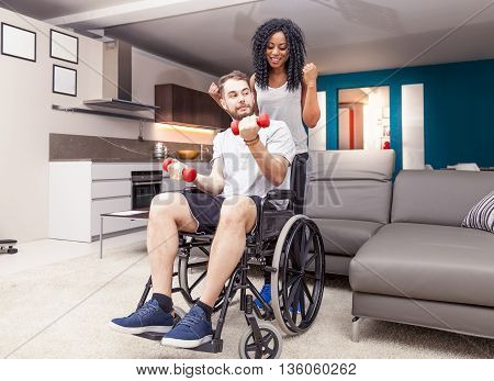 Young Girl Helps A Disabled To Rised Dumbbells