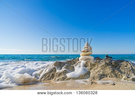 Stones pyramid on sand symbolizing zen, harmony, balance. Ocean in the background