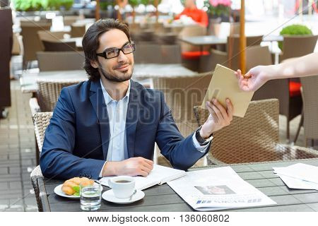 Successful young businessman is paying for his breakfast in restaurant. He is giving paid bill to female waitress. Man is sitting and looking at her flirtingly. He is smiling