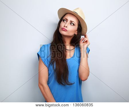 Happy Humorous Grimacing Woman In Summer Hat Thinking About Vacation And Looking Blue Background