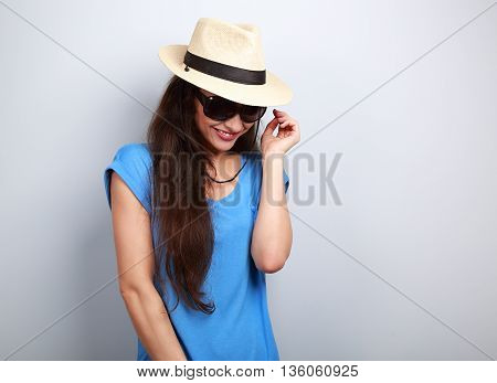Happy Casual Laughing Woman In Sun Glasses And Hat Looking Down On Blue Background