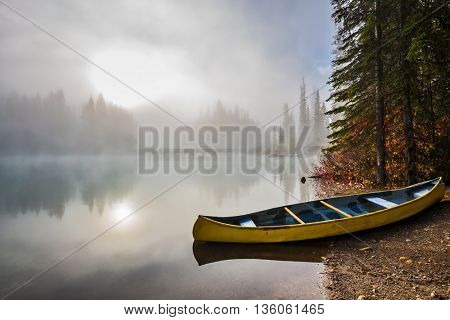 The sun peeps through the mist. Fishing boats moored on the shore. Emerald Lake in Yoho National Park
