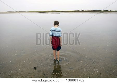 Boy wading in the water by the ocean.