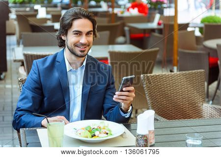 Confident young man is having breakfast in cafe. He is using mobile phone and smiling