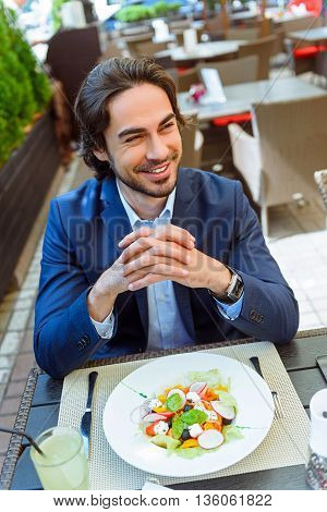 Joyful young businessman is relaxing in restaurant. He is sitting at table near a plate of fresh salad. Man is looking aside and laughing
