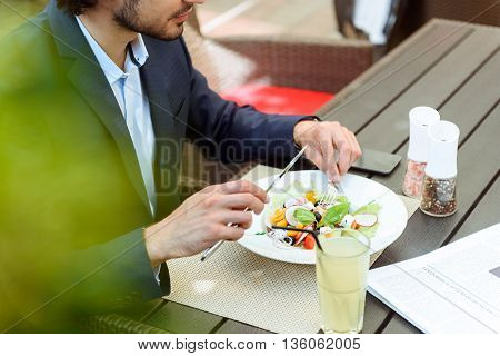 Young man eating salad in cafe. He is sitting at table in suit