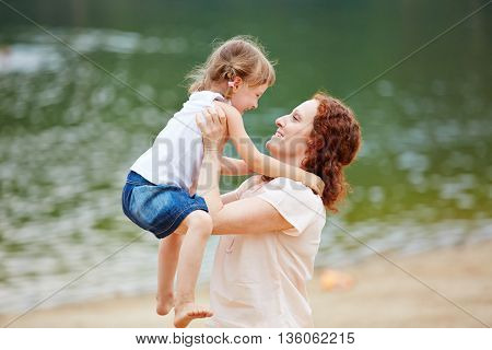 Happy mother lifting smiling daughter on a beach