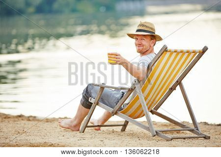 Relaxed man drinking beer in deck chair in summer