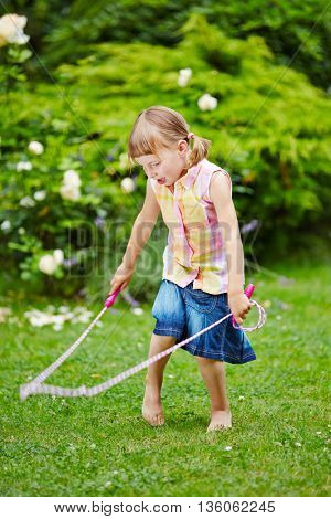 Girl playing with jump rope in garden in summer