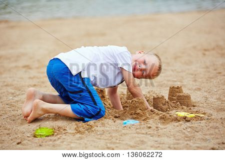 Boy building sand castle in summer on a beach