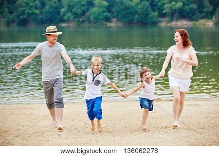 Family with two children at family vacation in summer at a beach