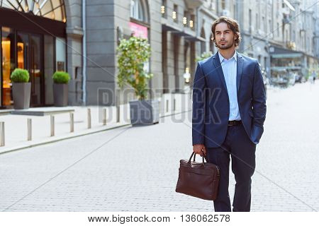 Confident young businessman is standing on street. He is holding a suitcase. Man is looking forward pensively