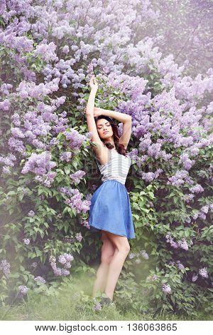 young woman near a large lilac bush