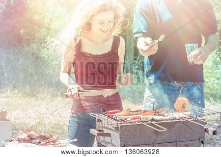 young couple cooking at barbecue grill in the backyard on a sunny day