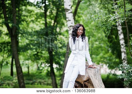 Portrait Of Stylish Black African American Girl Sitting On A Stump On Green Park