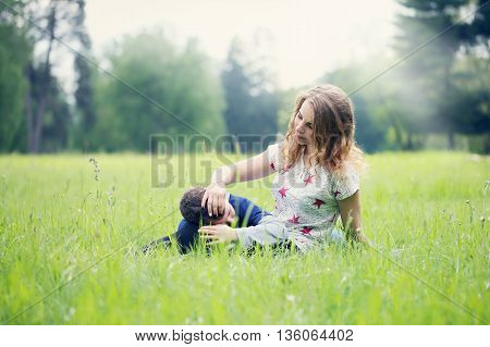 mother gently stroked her son resting on a meadow
