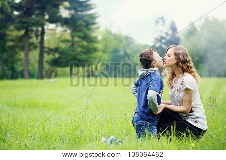 Young mother plays with her son in a meadow
