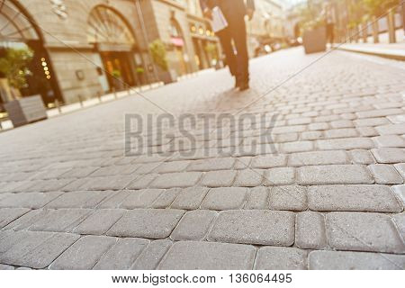 Concept of young man walking with newspaper on background. Focus on road