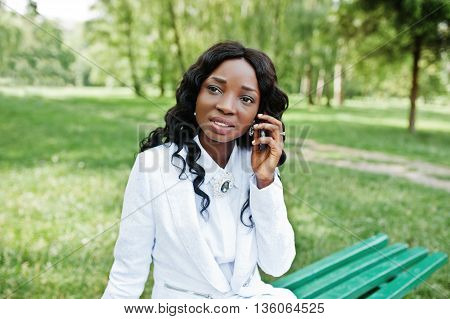 Portrait Of Pretty Black African American Girl Sitting On Bench At Green Park And Speeking On Mobile