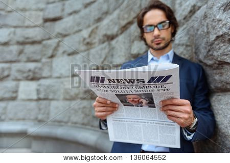 Serious young man is reading paper outdoors. He is standing near a wall in suit. Focus on newspaper