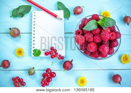 Ripe juicy raspberry in glass bowl with peppermint leaves on painted blue wooden background, blank notepad and red pencil, currant clusters, gooseberry and yellow chamomiles, summer fruits and flowers,  space for text, recipe or message
