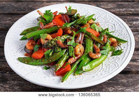 Shrimp and Asparagus stir fry food on white plate.
